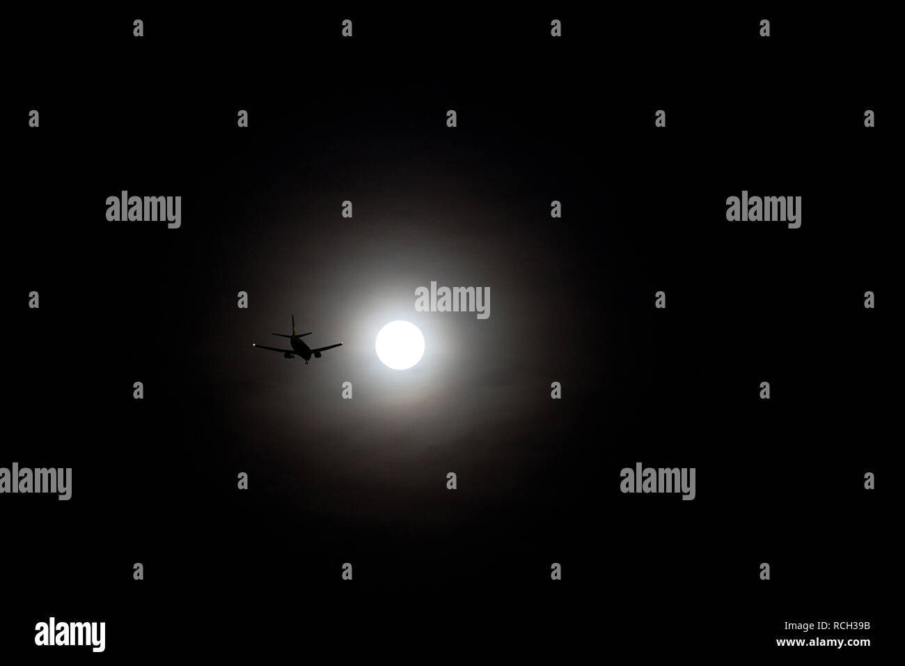 The silhouette of the plane takes off into the sky, illuminated by the light of the moon on a black background - Stock Image