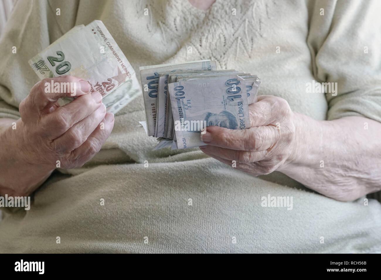 closeup wrinkled hands of senior woman counting money (turkish lira) Stock Photo