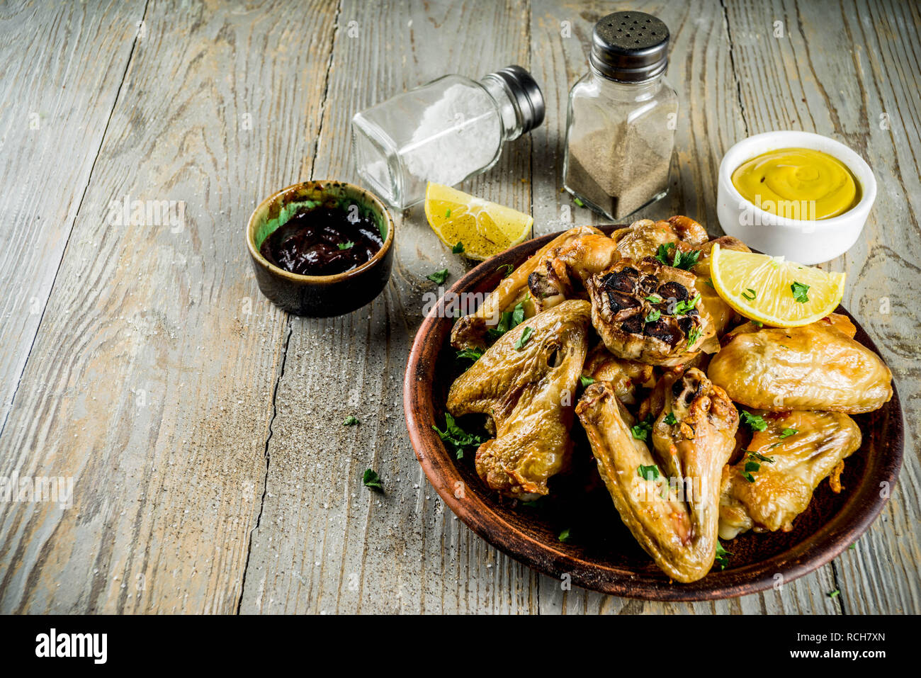 Grilled bbq chicken wings with sauces and spices, wooden background copy space top view Stock Photo