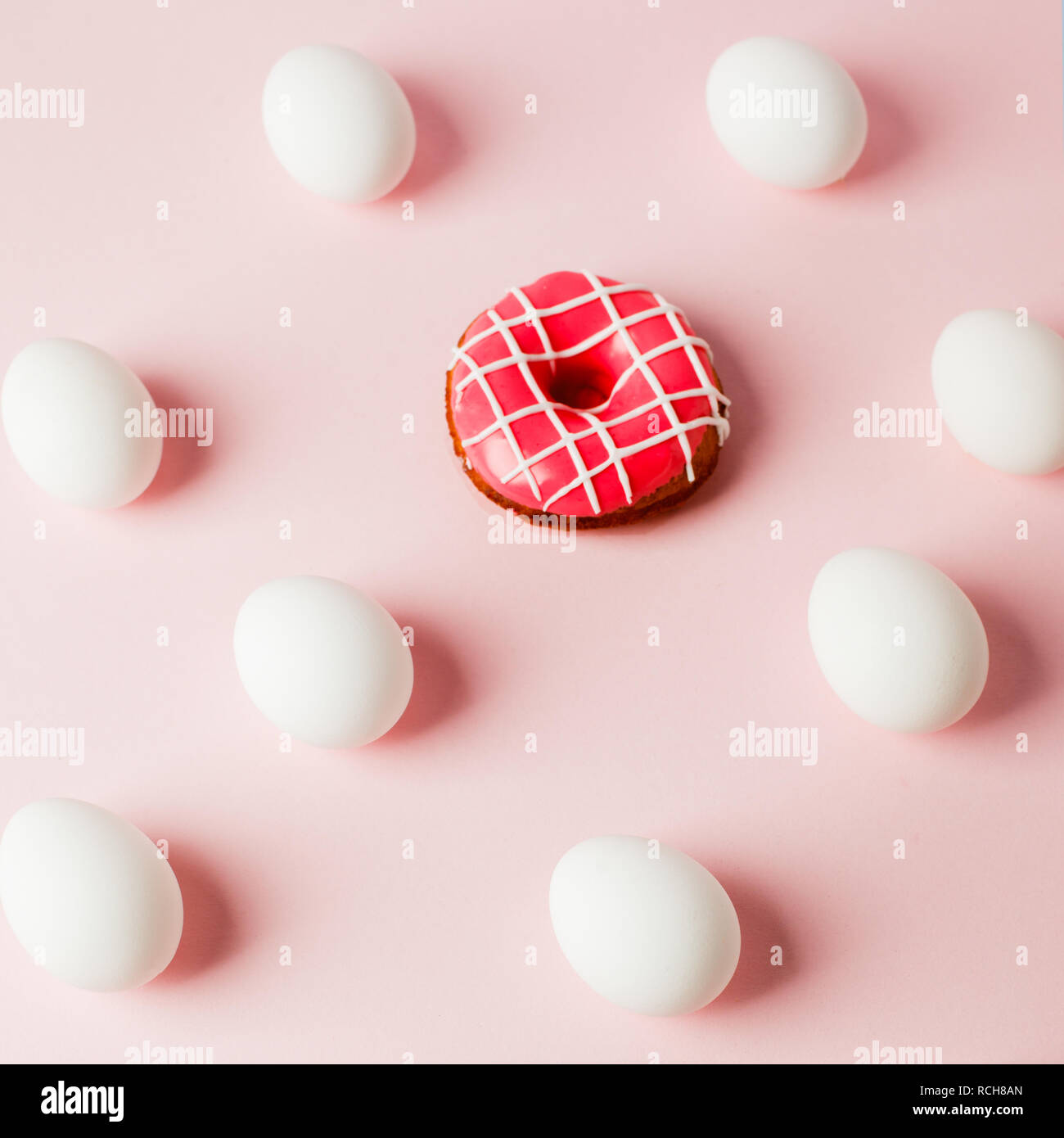 Easter white eggs repetition with shadow and pink donut on pink pastel background, system error, copy space, trendy background - Stock Image