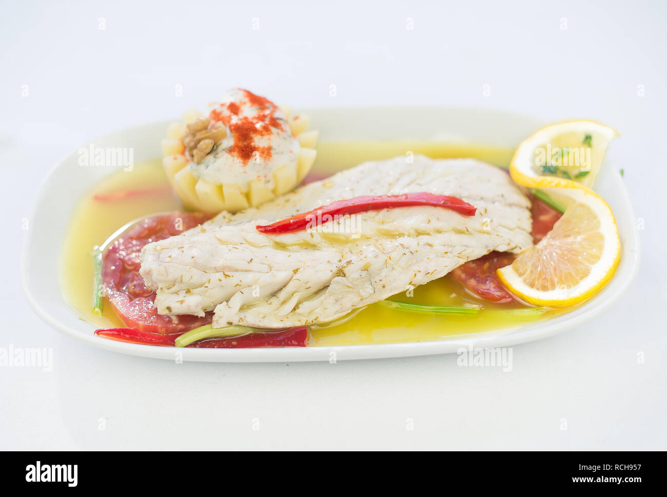 Grilled fish food. This grilled seafood fish dish on isolated white background.  Delicious healthy yummy tasty grilled seafood fish dish - Stock Image