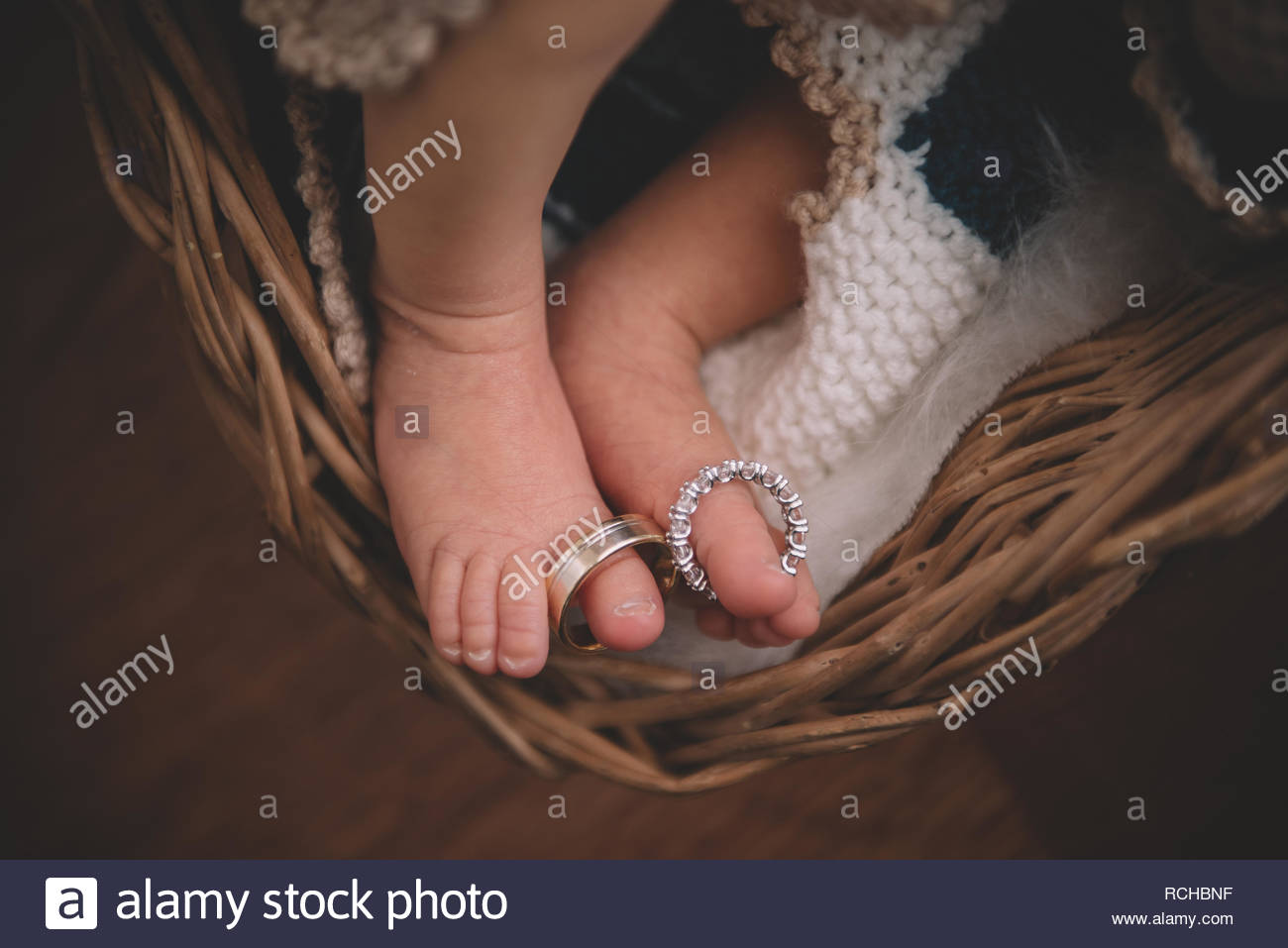 Sweet little cute baby toes with parent's wedding rings. Lovely family. Family ties. Baby and parents. Baby, mother and father. - Stock Image