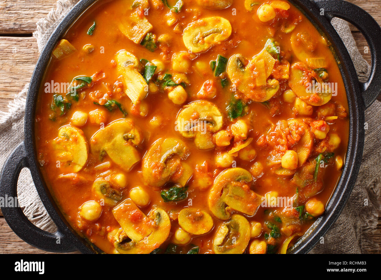 Freshly cooked mushroom curry with spinach, tomatoes and chickpeas close-up in a frying pan. horizontal top view from above Stock Photo