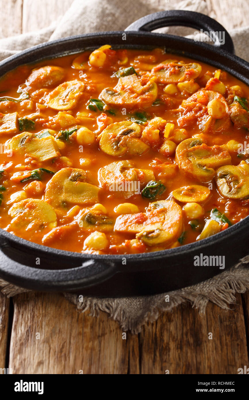 Spicy vegetarian mushroom curry with spinach and chickpeas close-up in a frying pan on the table. vertical Stock Photo