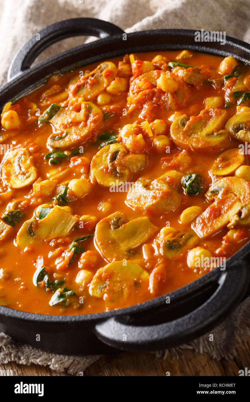 Mushroom curry with spinach and chickpeas close-up in a frying pan on the table. vertical Stock Photo