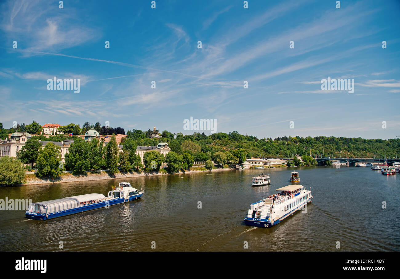 Prague, Czech Republic - June 03, 2017: river cruise ships and city skyline on sunny day on blue sky background. Tourist destination, vacation, travelling concept - Stock Image
