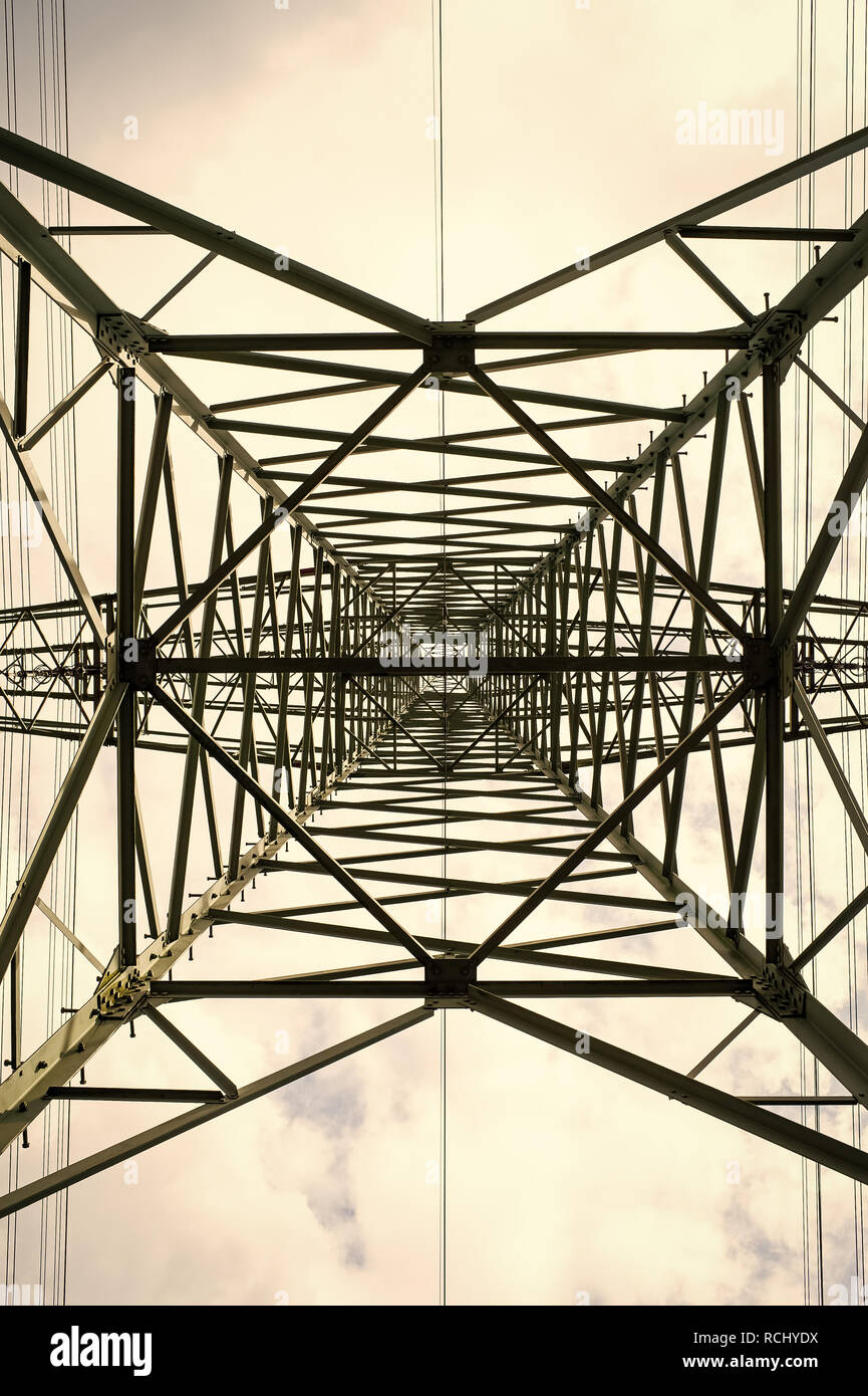 Transmission tower bottom view. Power tower on cloudy sky. Electricity pylon structure for power line. High voltage post outdoor. Energy and ecology. - Stock Image