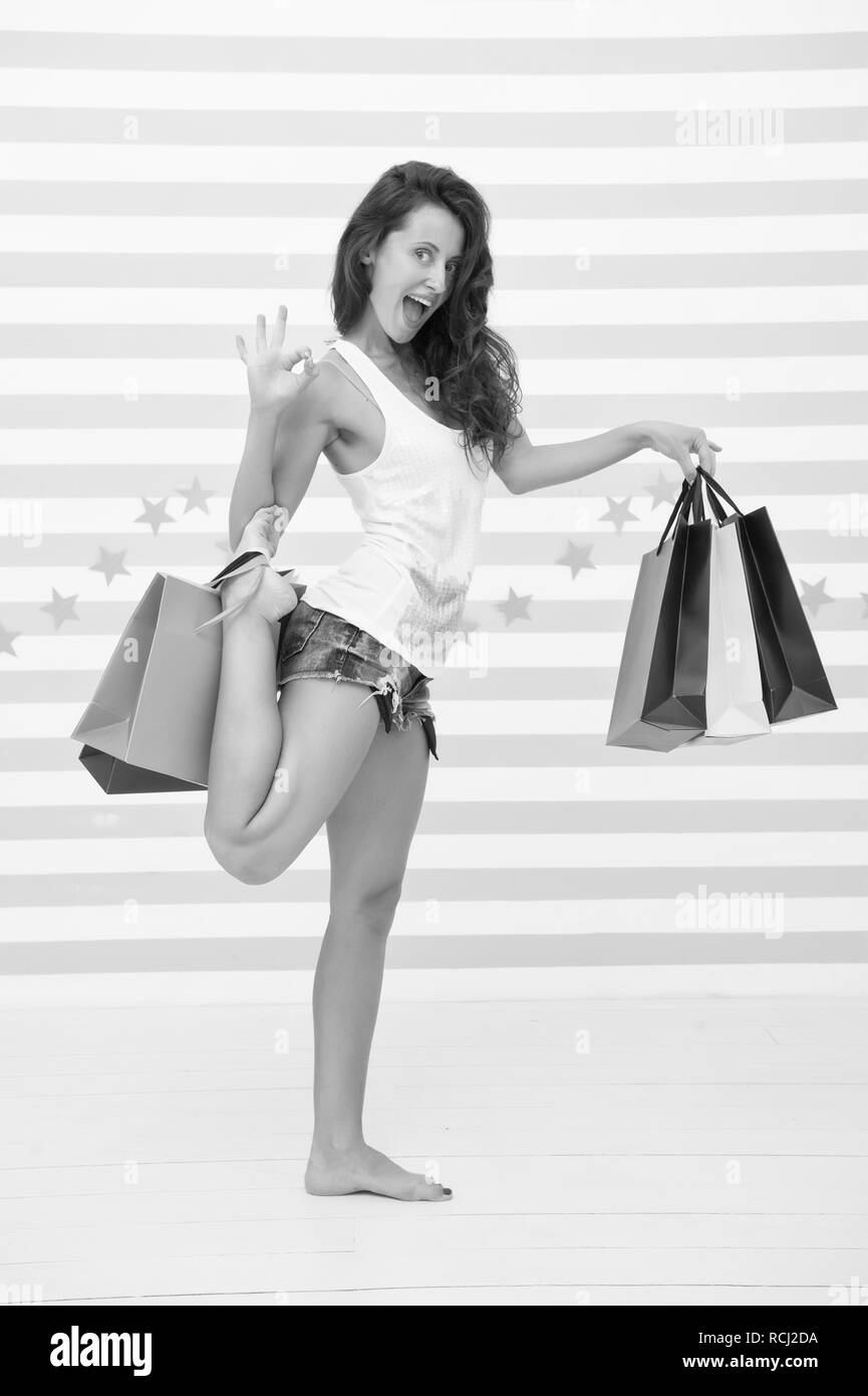 Too many packages to hold by only hand. Finally bought favorite brand. Tips shop sales. Girl satisfied shopping. Profitable purchase black friday. Woman carries bunch shopping bags striped background. - Stock Image