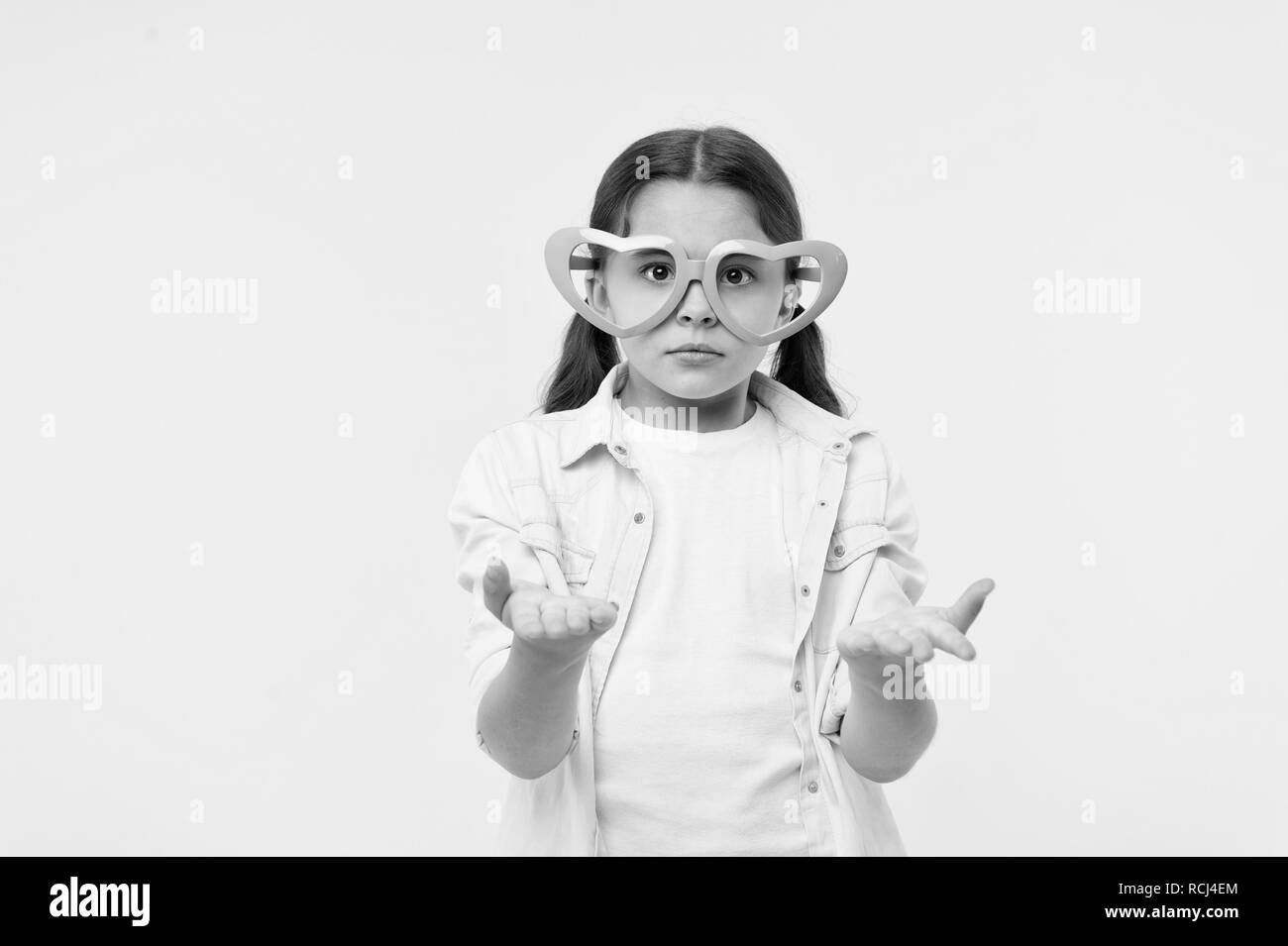 Kid girl heart shaped eyeglasses looks disappointed. Girl wear cute eyeglasses disappointed face. What just happened. She asks you. Child dissapointed confused what going on. Disappointment concept. - Stock Image