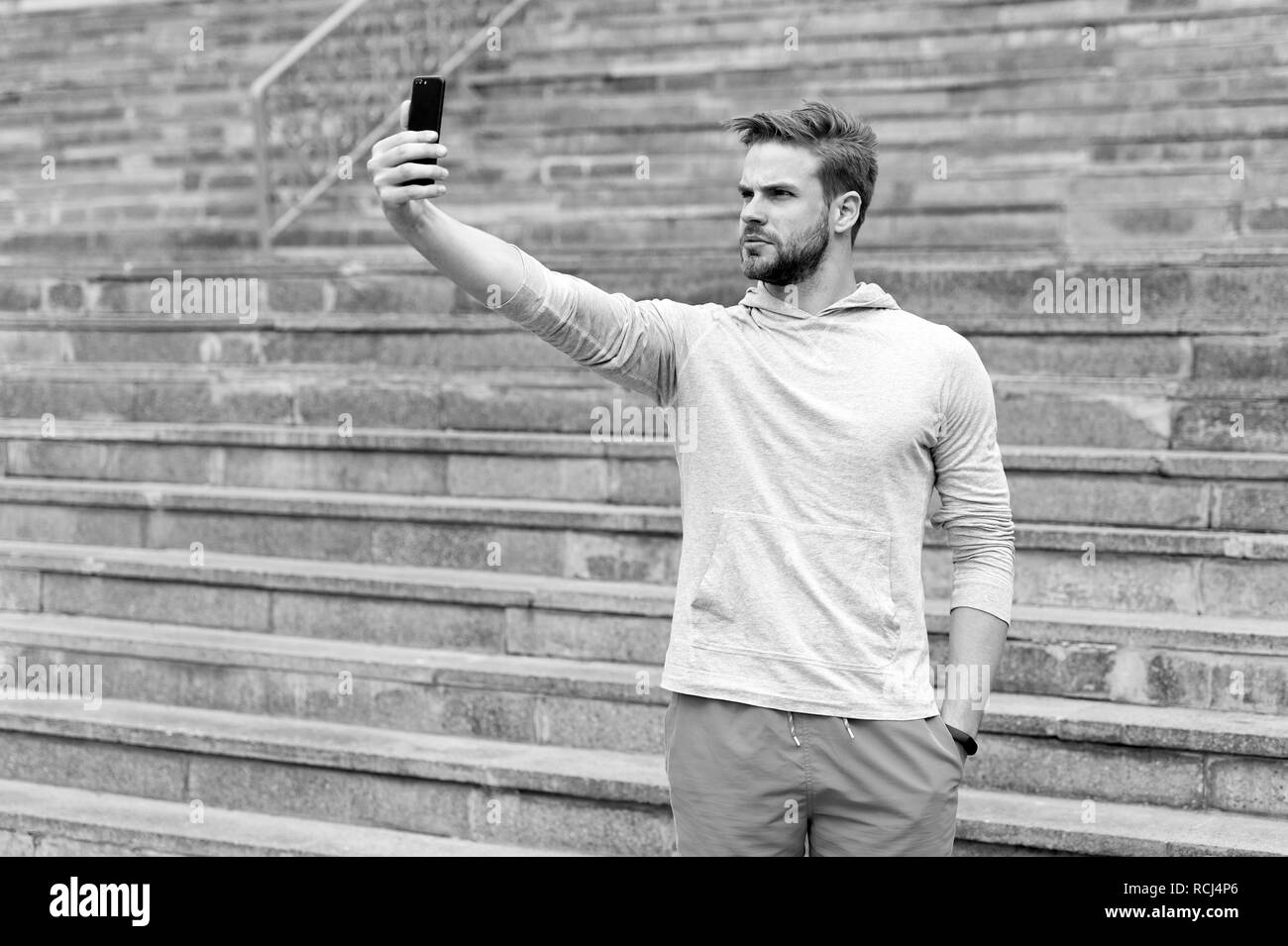 Selfie concept. Handsome man take selfie with smartphone. Athletic guy use mobile phone for selfie. Selfie before training. - Stock Image