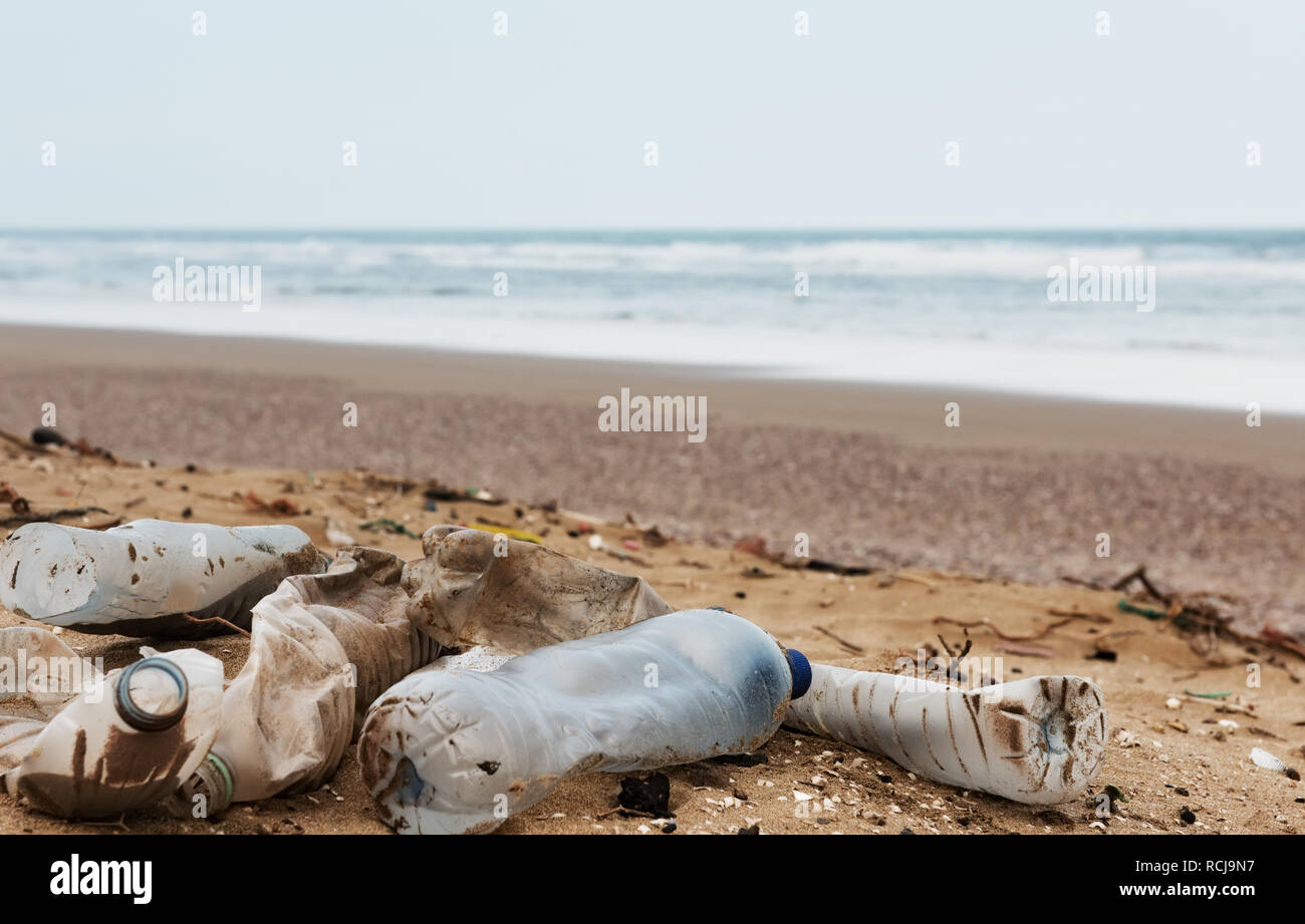 Beach pollution. Plastic bottles and other trash on sea beach - Stock Image