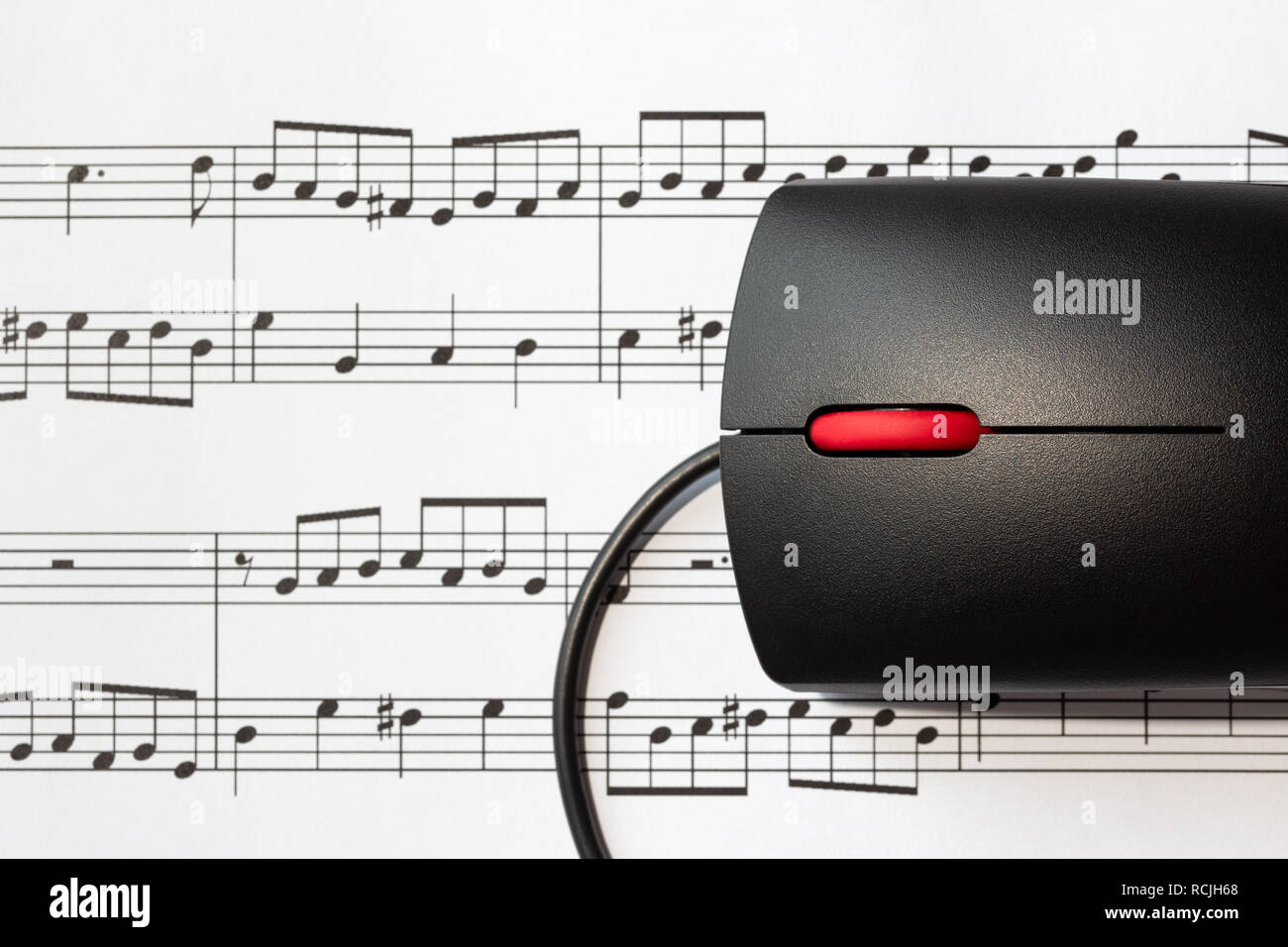 Computer mouse on a sheet with musical notes, close-up with