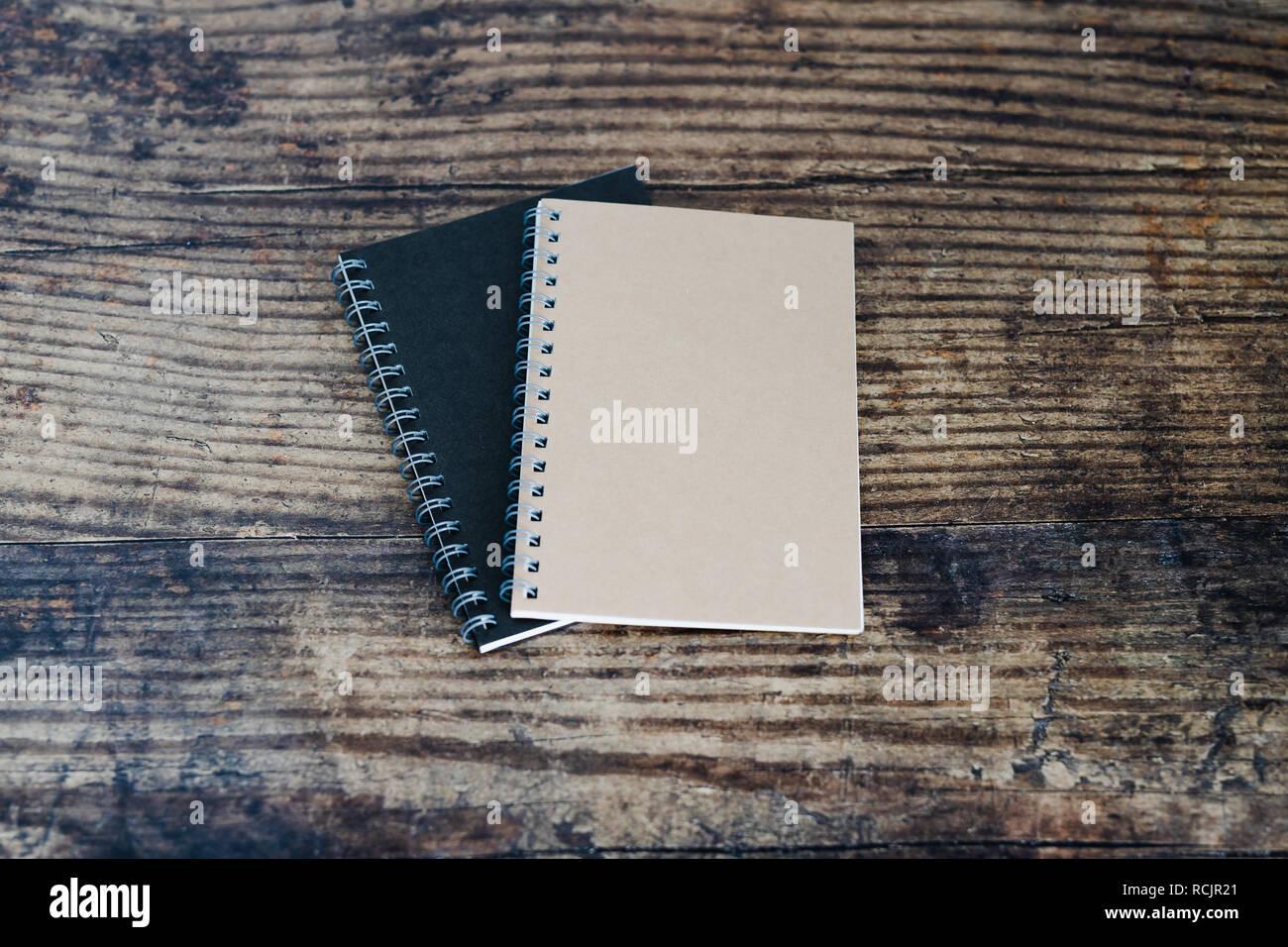 minimalist desk setting flatlay with notepads on dark wooden