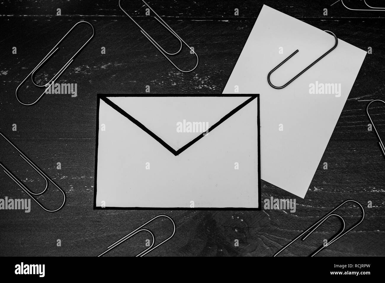 funny metaphor of inbox with email envelop and attachment clip on real-life desk, flatlay shot from topdown perspective - Stock Image