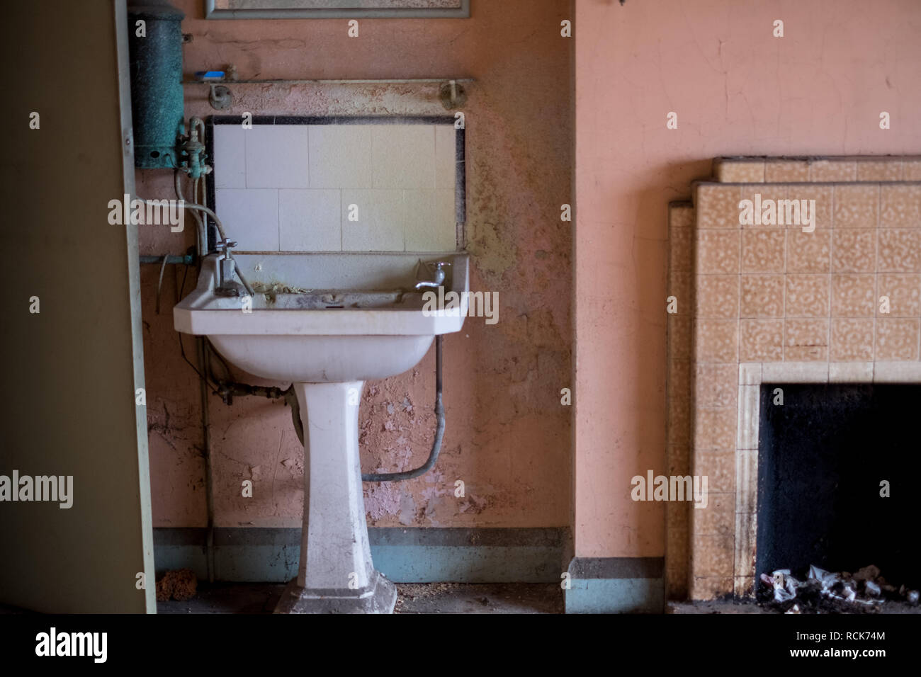 Close up of hand basin and original oxidised water heater in derelict house built in 1930s deco style, Rayners Lane, Harrow, Middlesex, UK - Stock Image