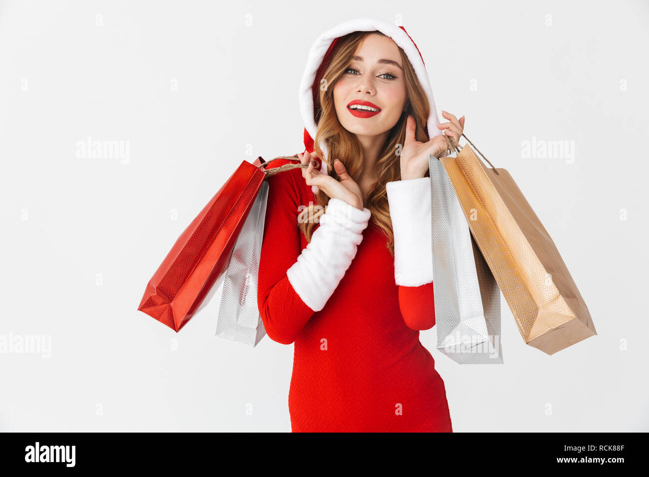 8d7a337990686 Portrait of cheerful woman 20s wearing Santa Claus red costume smiling and  holding colorful paper shopping