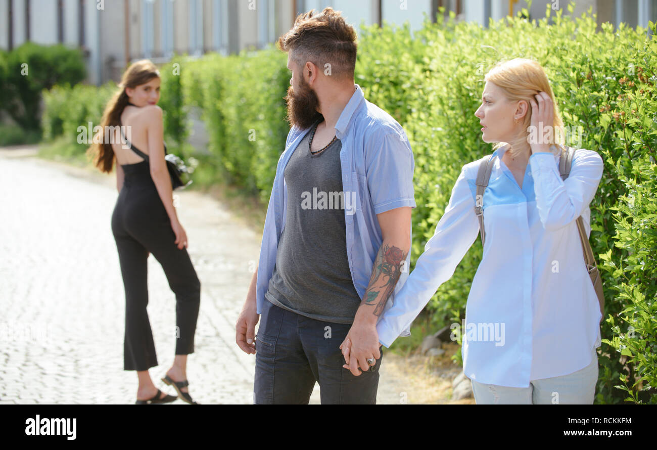 He is a cheater. Man cheating his wife or girlfriend. Love triangle and threesome. Bearded man looking at other girl. Hipster choosing between two women. Betrayal and infidelity. Unfaithful love - Stock Image