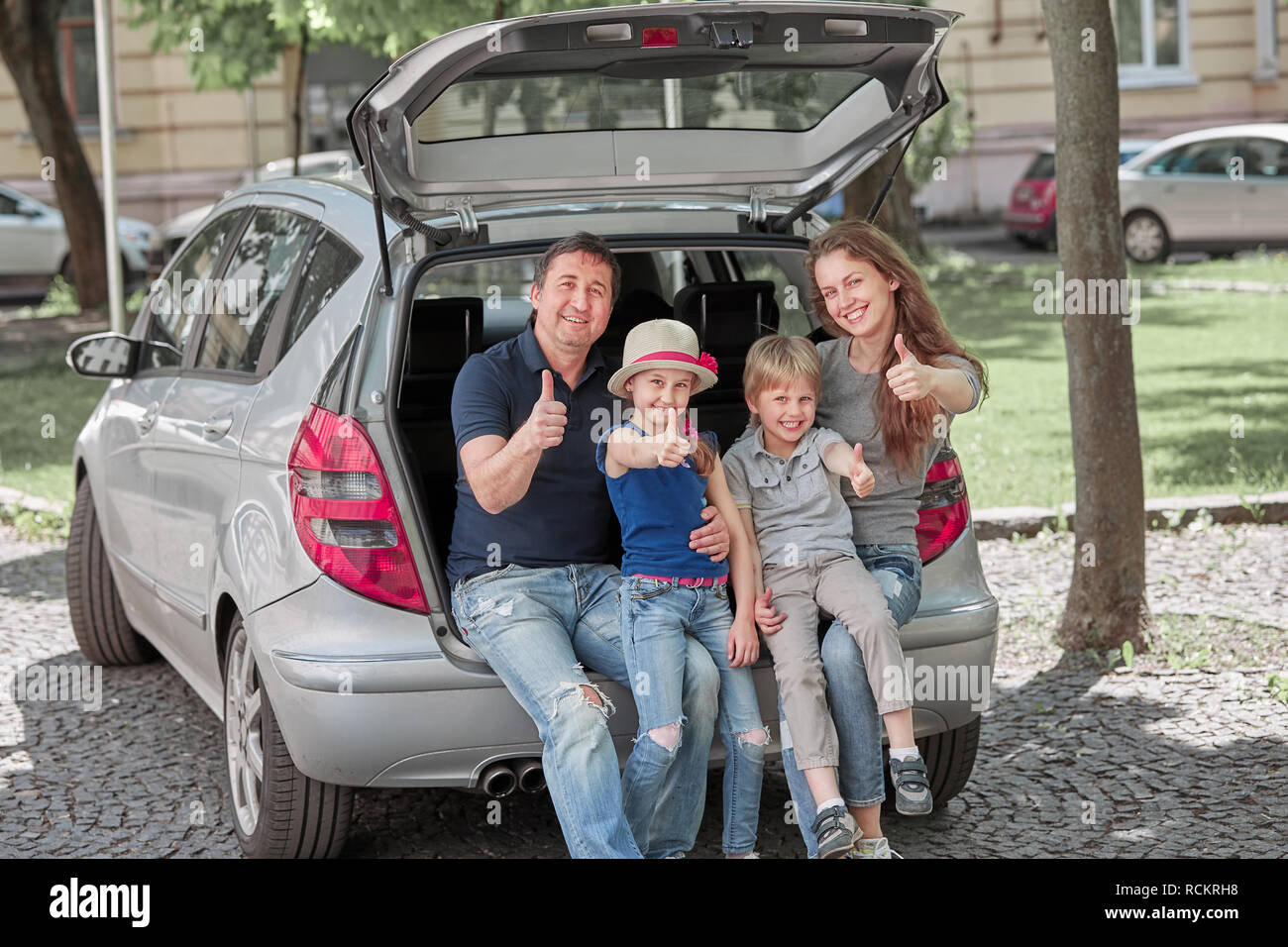 family sitting in the trunk of a family car and showing thumbs up - Stock Image