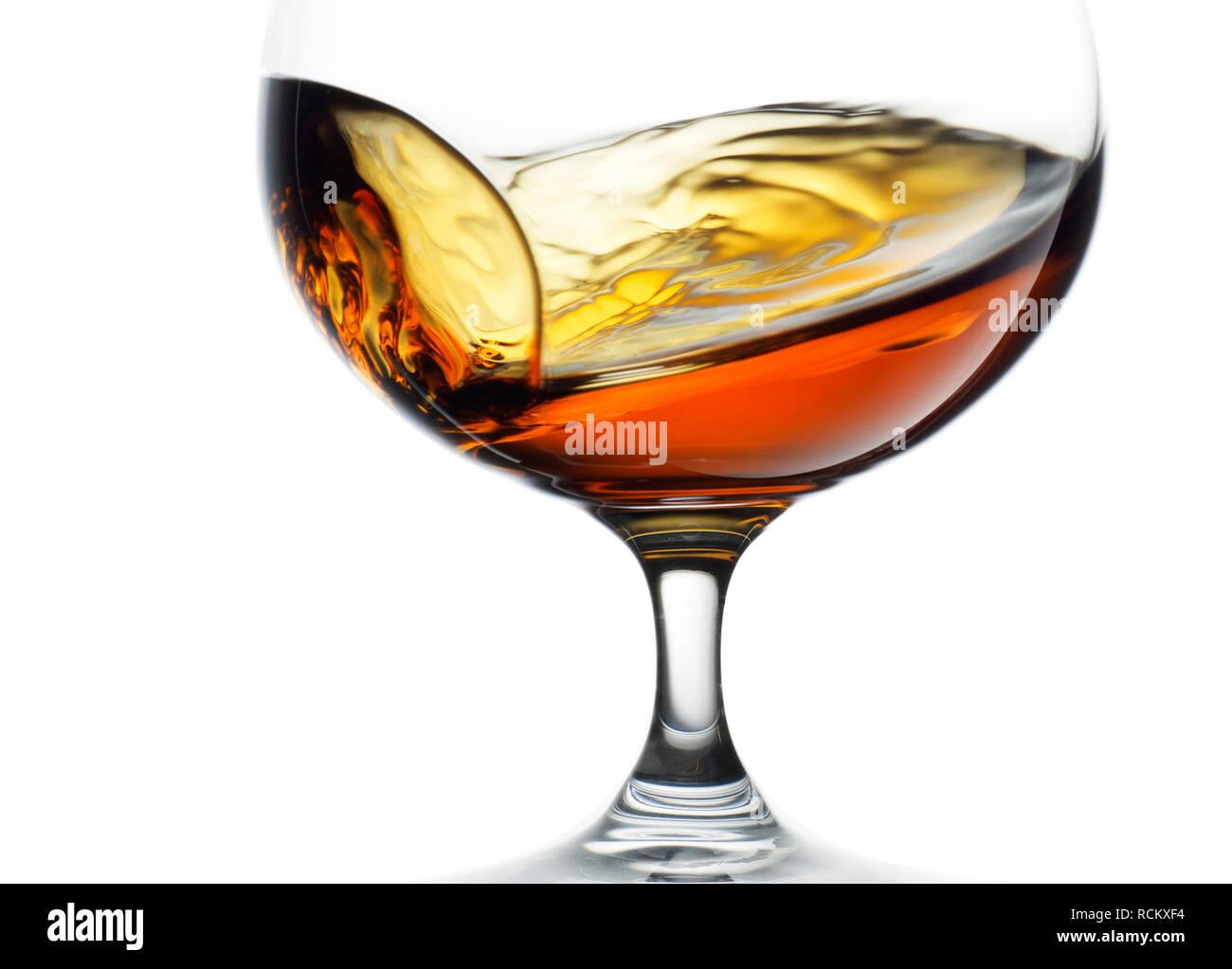 Glass of cognac brandy, back lit, plain background, cropped - Stock Image