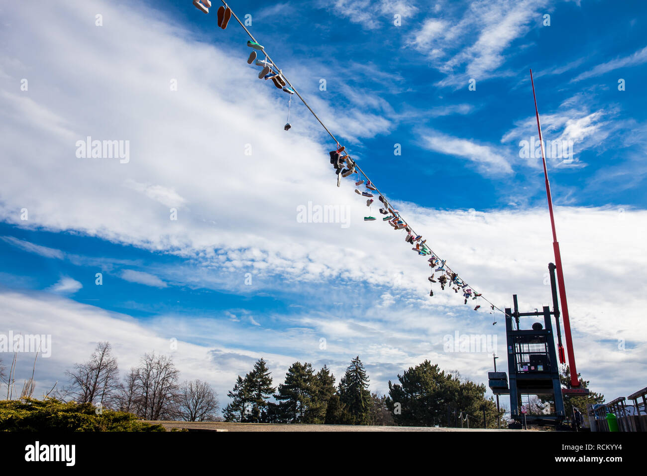 PRAGUE, CZECH REPUBLIC - APRIL, 2018: Shoes hanged at the power lines next to the metronome at the Letna hill view point - Stock Image