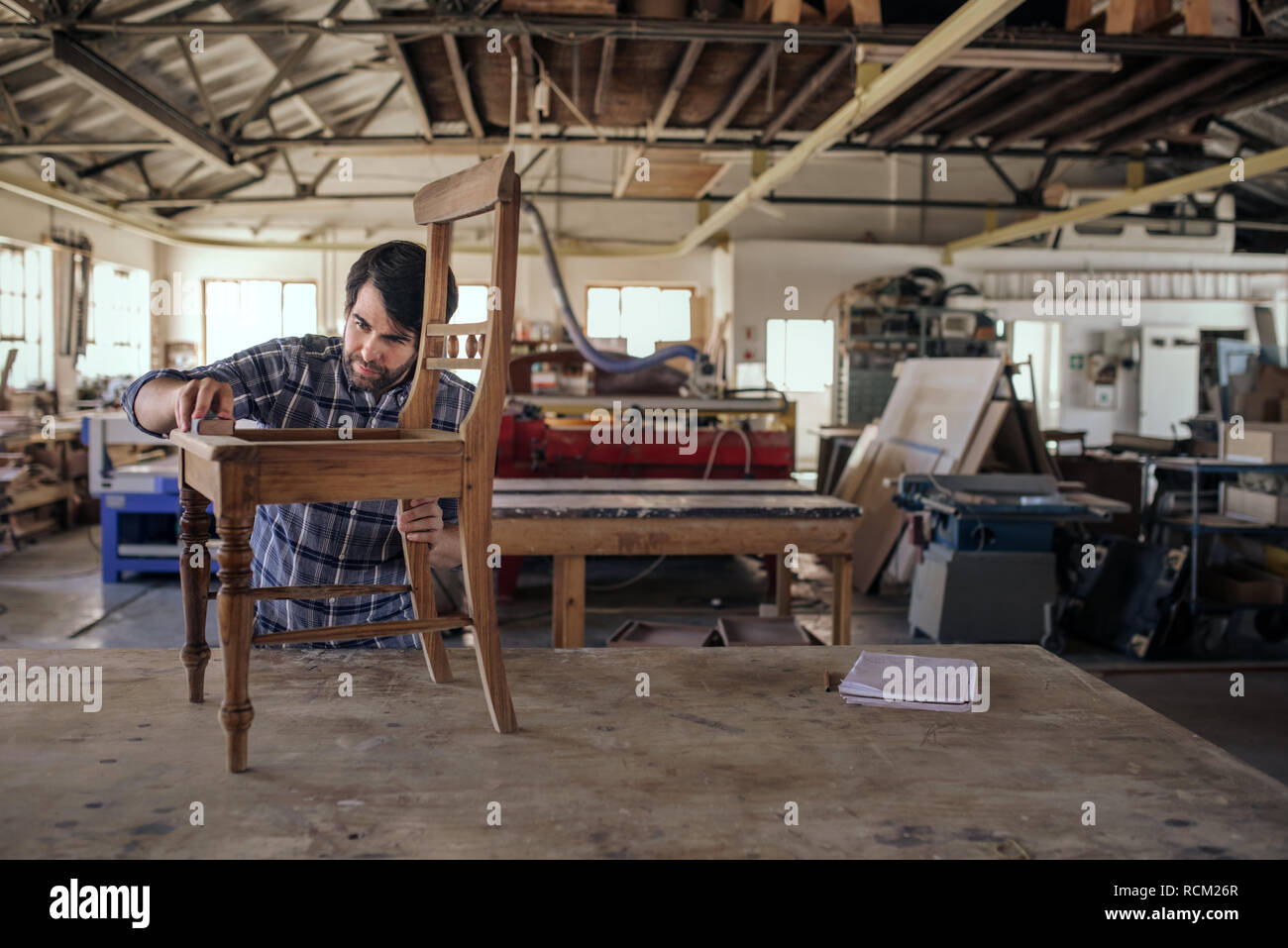 Woodworker sanding a chair on his workshop table - Stock Image
