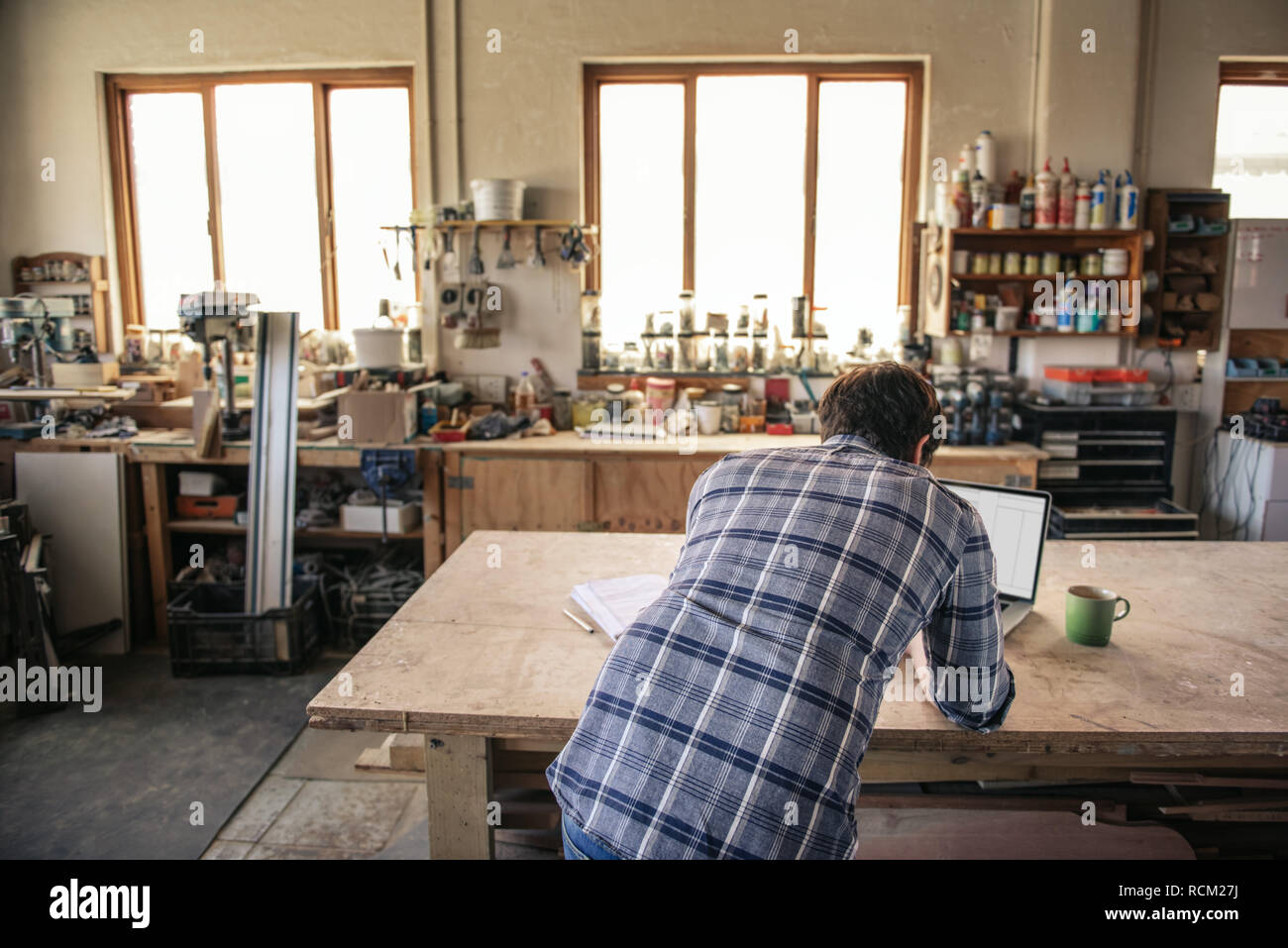 Woodworker using a laptop at his workshop bench - Stock Image