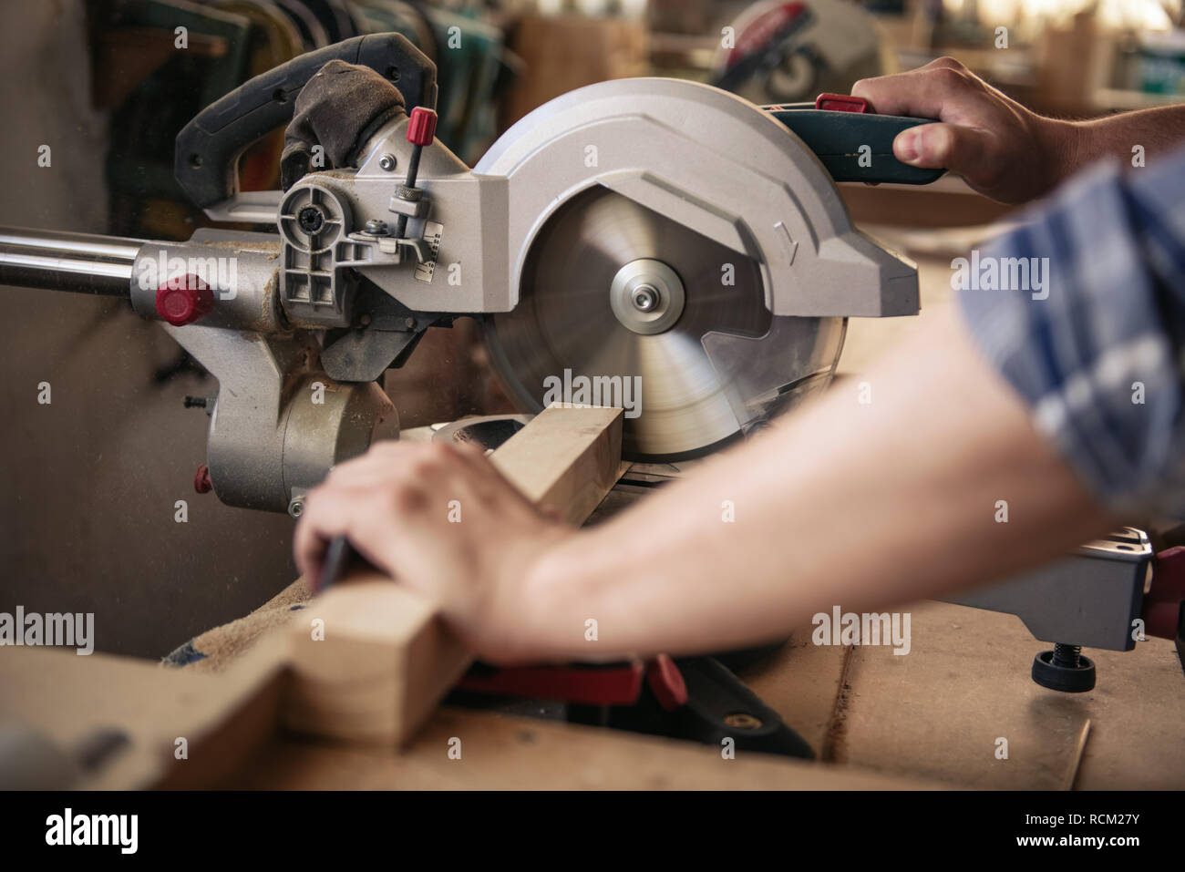 Woodworker sawing wood in his carpentry workshop - Stock Image