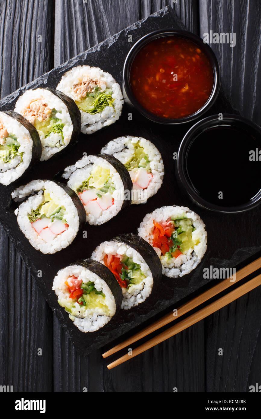 Futomaki rolls with various fillings are served with sauces close-up on a slate board on the table. Vertical top view from above Stock Photo