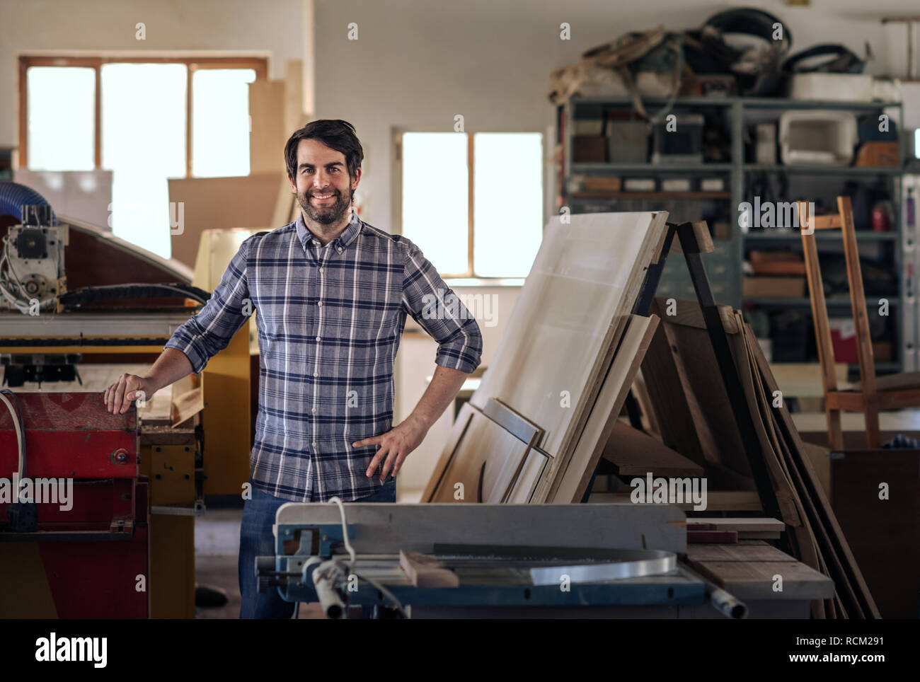 Woodworker smiling while standing by equipment in his workshop - Stock Image