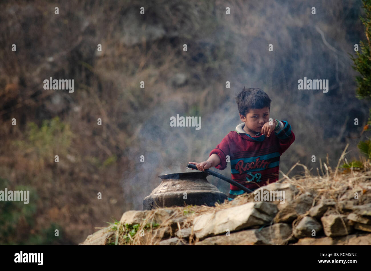 A young boy preparing hot water for a bath in Rashol, Himachal Pradesh. - Stock Image