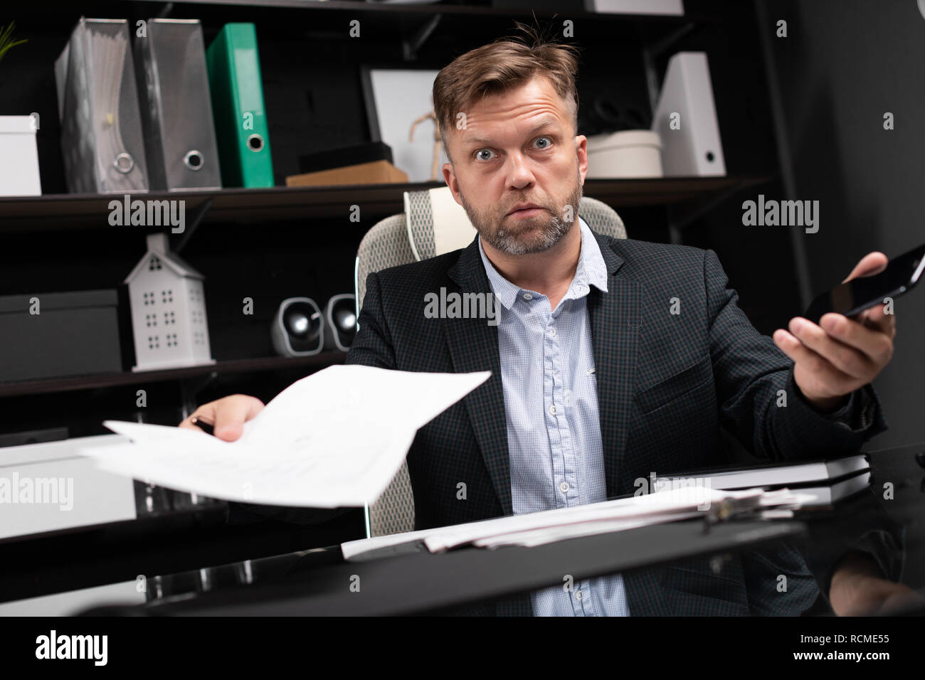 young man in business clothes working at computer Desk with phone and documents - Stock Image