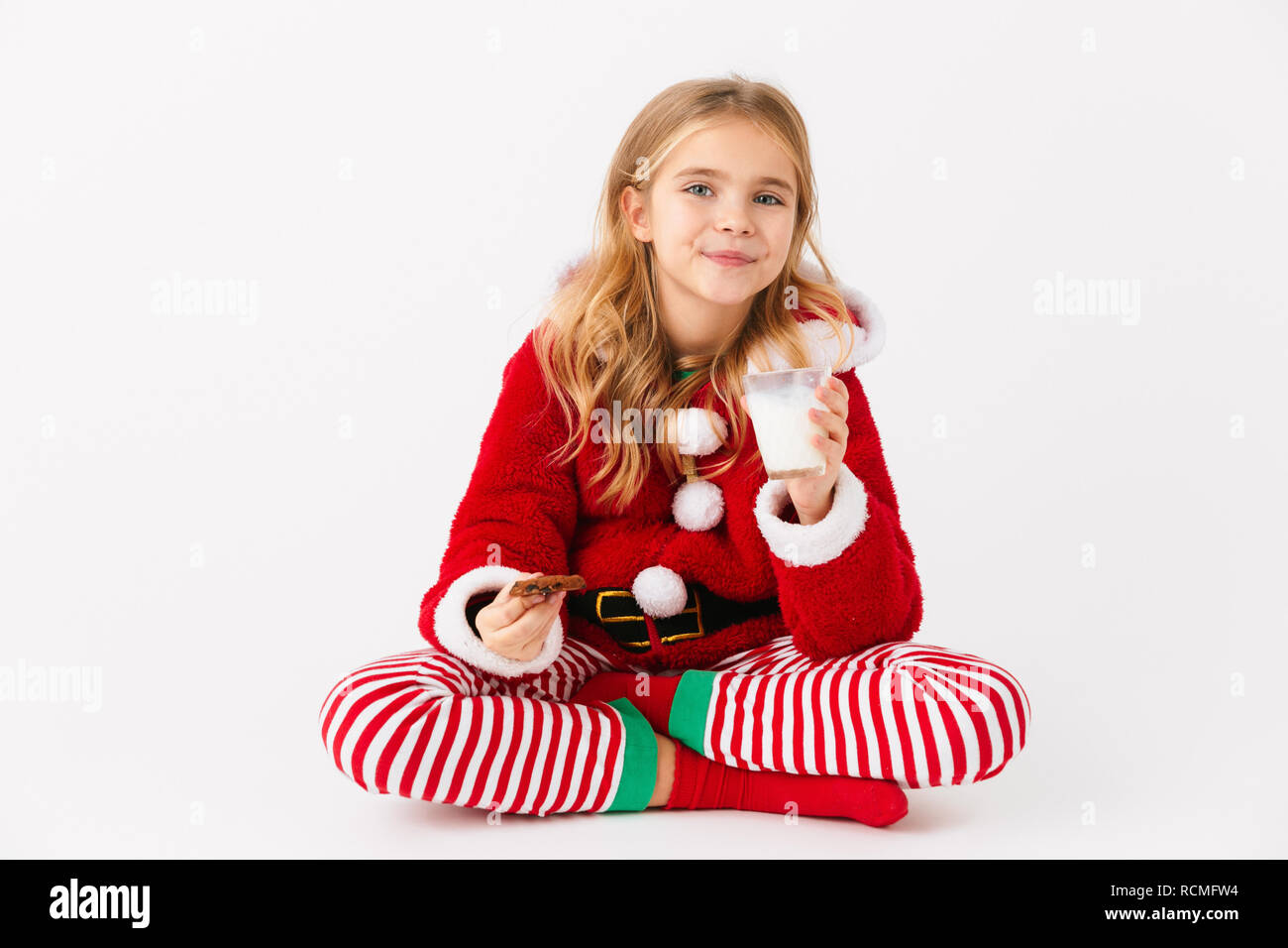 ee2a8c7449ec Cheerful little girl wearing Christmas costume sitting isolated over white  background, eating cookie with milk