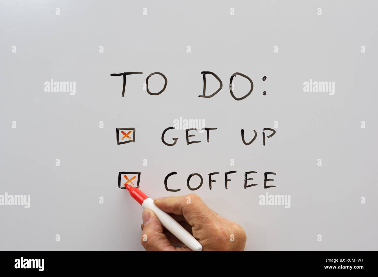 a hand with a dry erase marker checking off a to do list with get up and coffee on a whiteboard - Stock Image