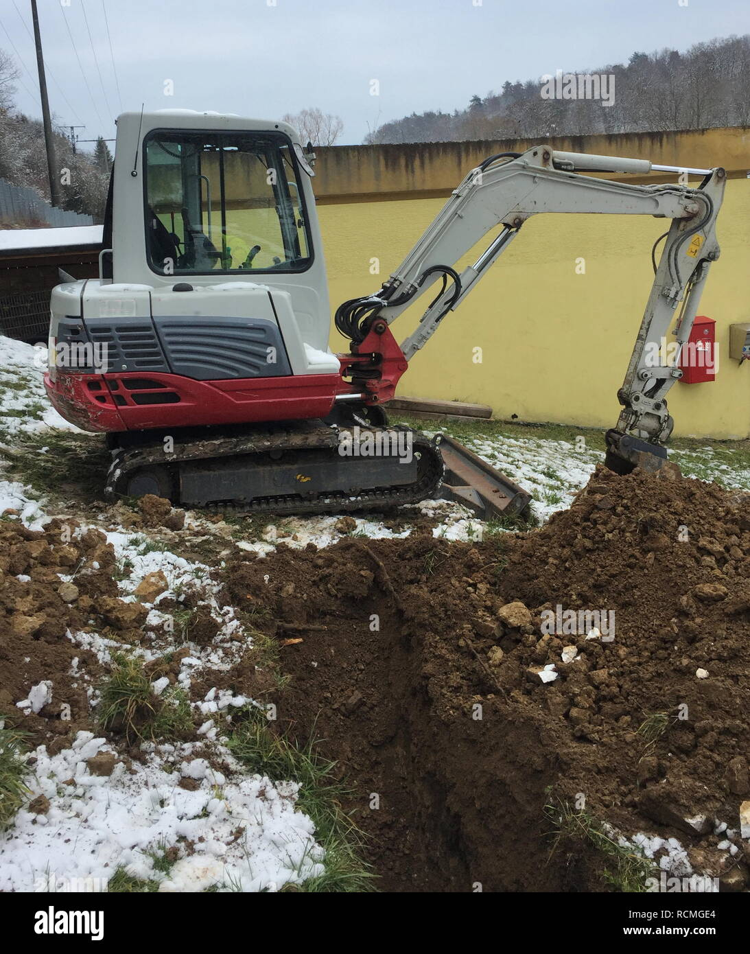 Excavator shovel digs into a ground covered with snow. - Stock Image