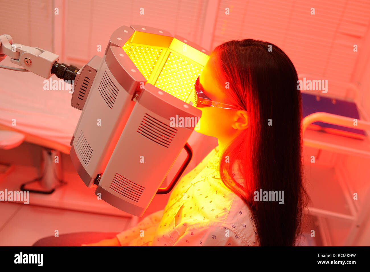The girl goes through a course of skin rejuvenation with the help of red light treatment. - Stock Image