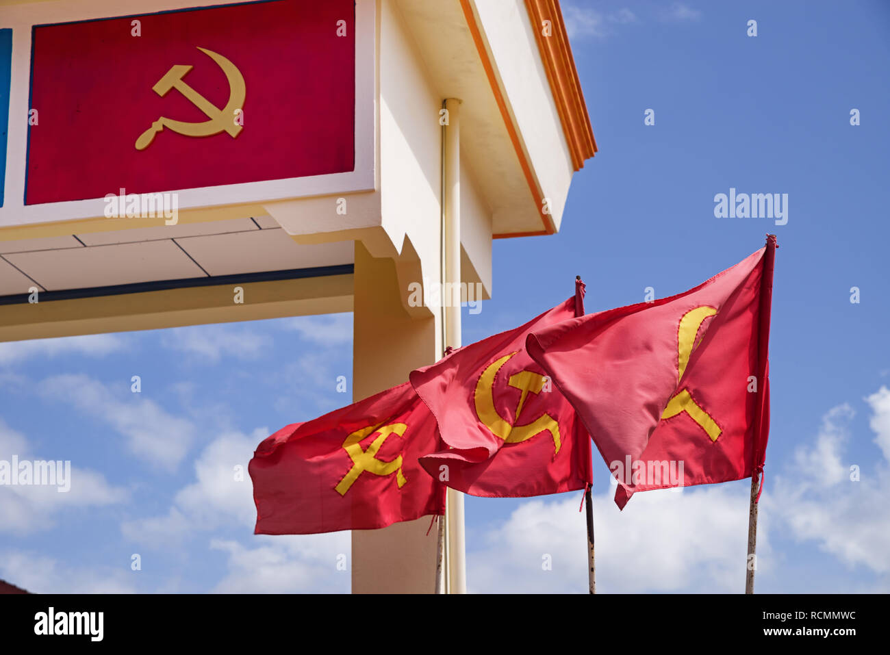 yellow and read hammer and sickle flags and decoration on an arch in Laos these are the flag of the Lao People's Revolutionary Party - Stock Image