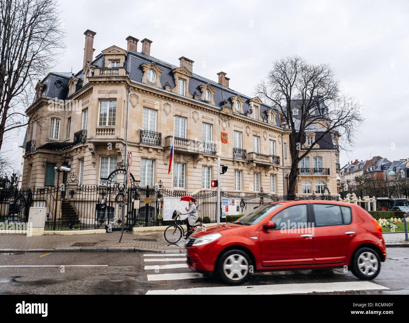 STRASBOURG, FRANCE - MAR 28, 2018: Cars driving in front Russian Consulate Embassy half-mast Russian Flag tribute mourning of victims fire at Zimnyaya Vishnya Winter Cherry shopping centre Kemerovo - Stock Image
