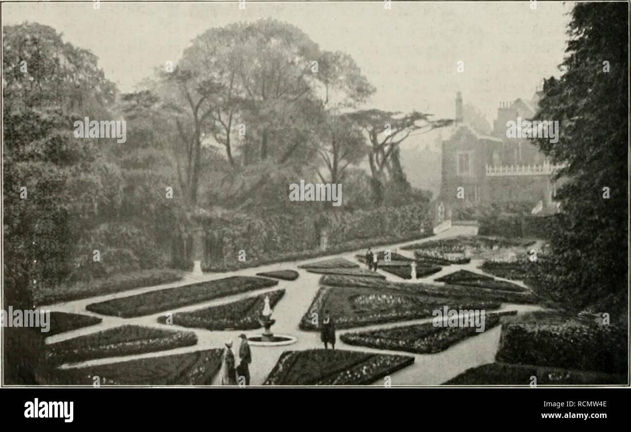 """. Die Gartenkunst. Landscape gardening; Gardens -- Europe. 98 DIE GARTENKUNST. XII, 6 !""""â """""""" -^cBBa^H^^nr Â«BvvnH . -* '.  ^^â R'^Ml râ ^^^^^^K4^ W Ã?'' ^ Uji.â ;â¢,;, rj»»«X»«ll»V'Â« 5^)?^ ^^^^^^f^^^^^^^M ^^â =^1 ^ ^ *^ â ^^^^^^^^^^^M^ At ⢠"""" . B Aus Holland-House Garden: Parkeingang an der Vorfahrt zum Hause. Raumwirkung besitzt. Die Verhältnisse der einzelnen Gartenteile stehen in seltener Harmonie und das Ganze sowohl, wie das Einzelne zeigt eine Fülle malerischer Reize. Und trotzdem das Ganze doch eine groÃe, vornehme Besitzung ist, herrscht in diesen Gartent Stock Photo"""