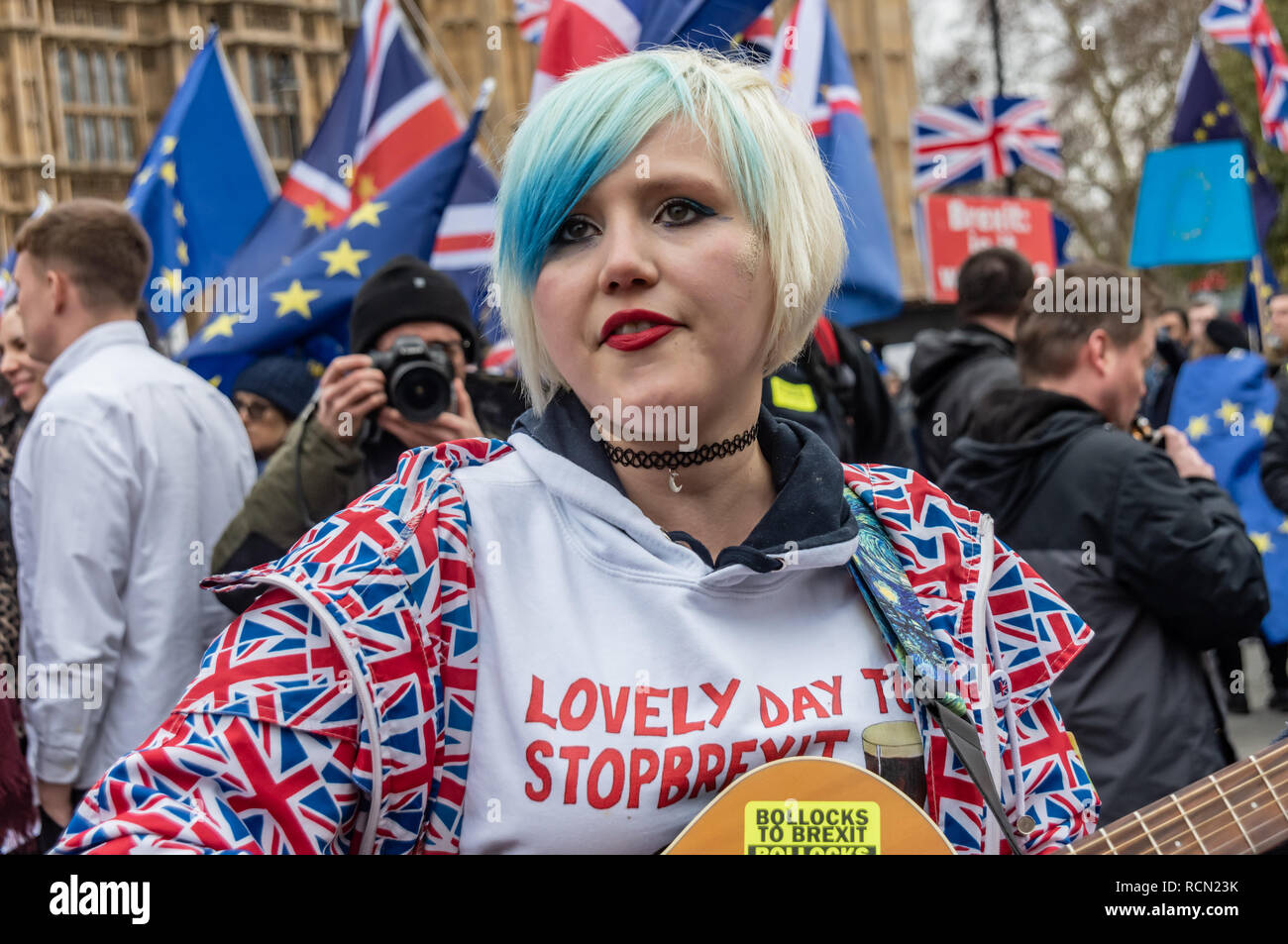 London, UK. 15th January 2019. EU Supergirl Madeleina Kay (Alba White Wolf) begins to sing about Europe. Groups against leaving the EU, including SODEM, Movement for Justice and In Limbo and Brexiteers Leave Means Leave and others protest opposite Parliament as Theresa May's Brexit deal was being debated.  While the two groups mainly kept apart, a small group, some in yellow jackets came to shout insults at pro-EU campaigners, while police tried to keep the two groups separate. Credit: Peter Marshall/Alamy Live News - Stock Image