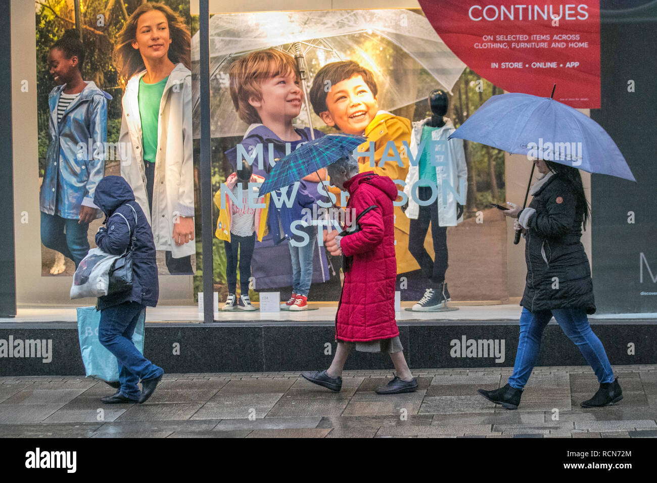 Preston, Lancashire, 16th Jan 2019. UK Weather. Wet & windy start to the day in the city centre. Rain is moving east across England with heavy showers in the north and west, turning increasingly wintry. People assing M&S sale window, discounts, clearance, reductions, banner, womens fashions, display, as the Sale continues. Credit: MediaWorldImages/Alamy Live News - Stock Image