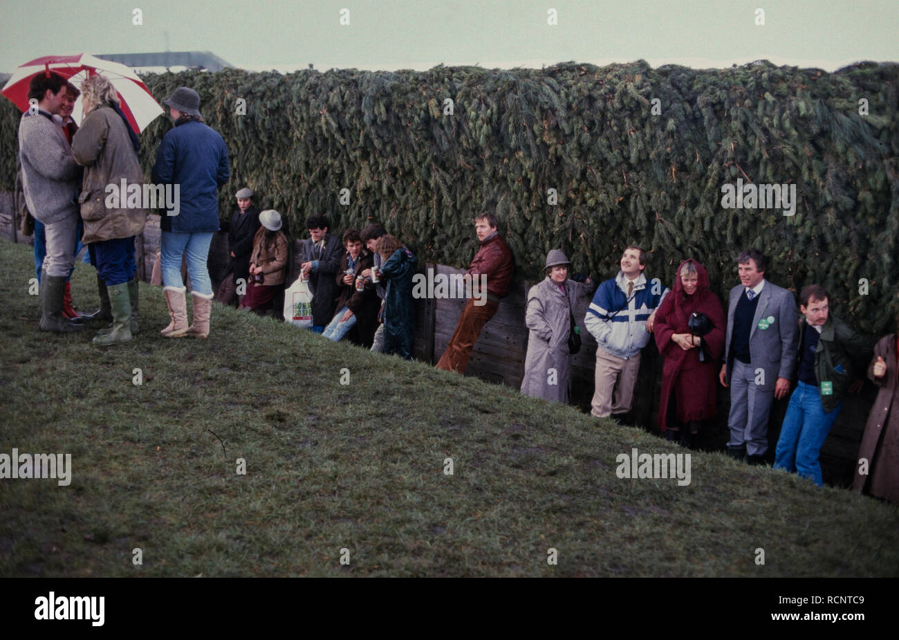 Grand National Horse race, Aintree, Liverpool, England UK. 1985 Spectators shelter from the rain in the lee of Bechers Brook fence. Stock Photo