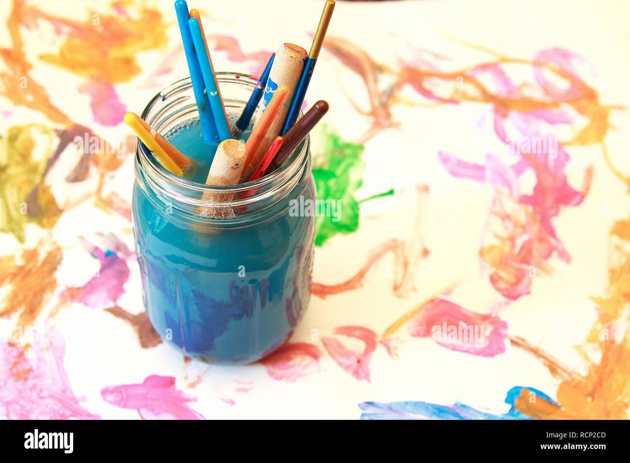 Kid's Messy paint brushes soaking in a glass jar of soapy water. Stock Photo
