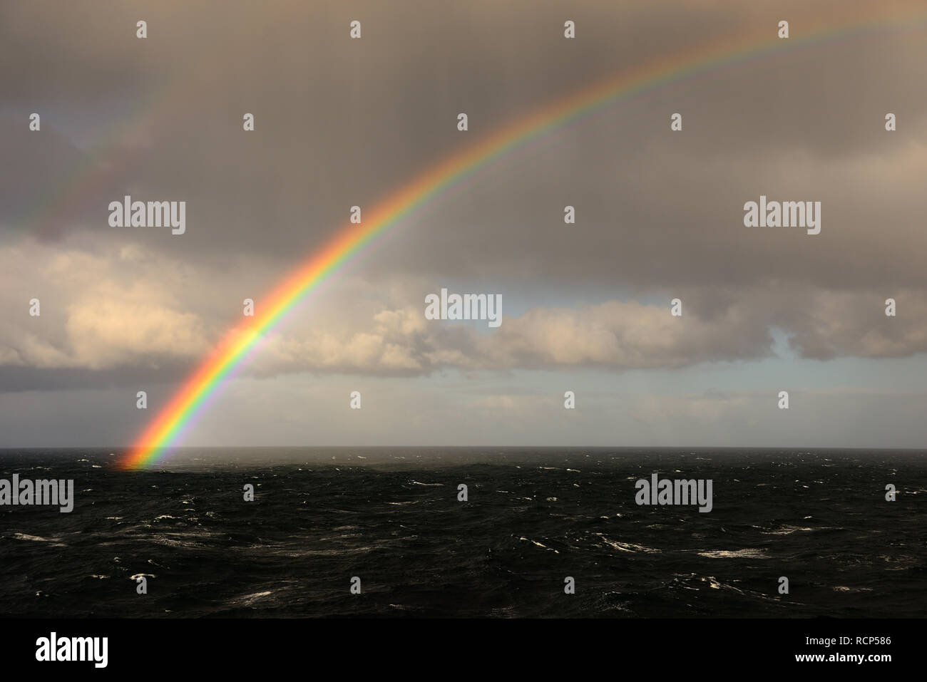 Rainbow over the ocean. - Stock Image