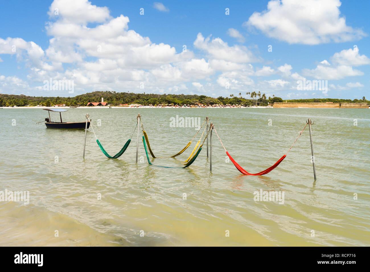 Hammocks in the ocean, by the shore of Coroa do Aviao islet - popular tourist destination in the north coast of Pernambuco - Stock Image
