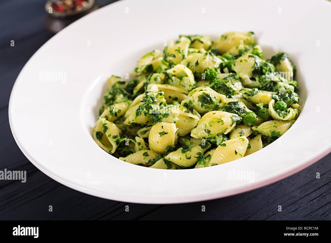 Conchiglie pasta with spinach and green pea pesto. Italian Cuisine. Vegan food. Stock Photo