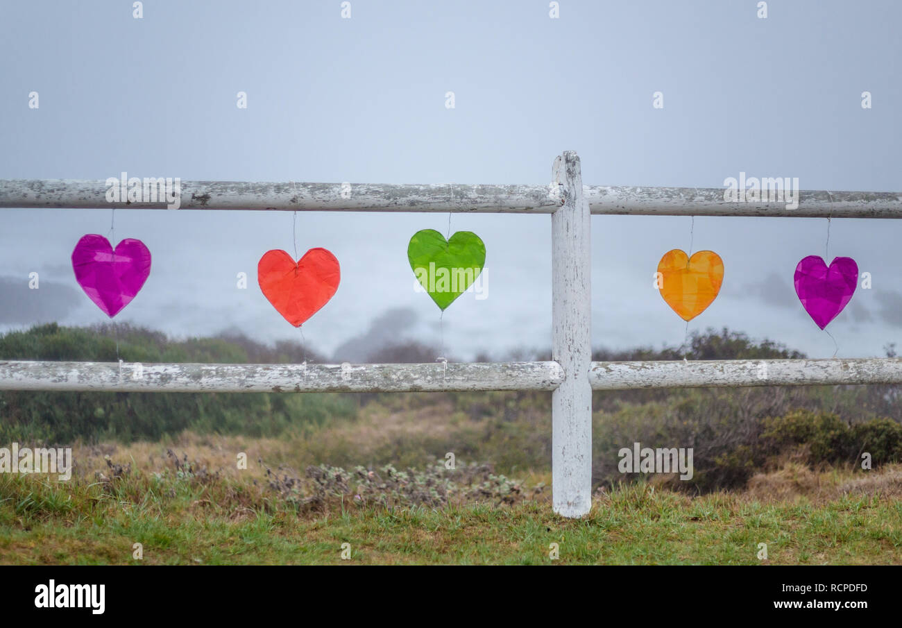 Wooden fence with colored hearts strung in a row - Stock Image