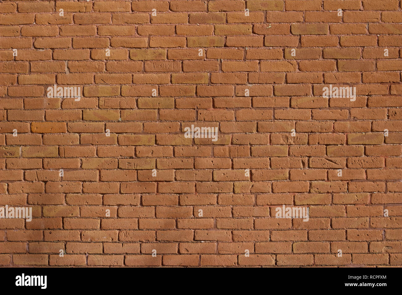 Antique weathered brick wall background abstract with deteriorating red clay bricks in traditional running bond pattern Stock Photo