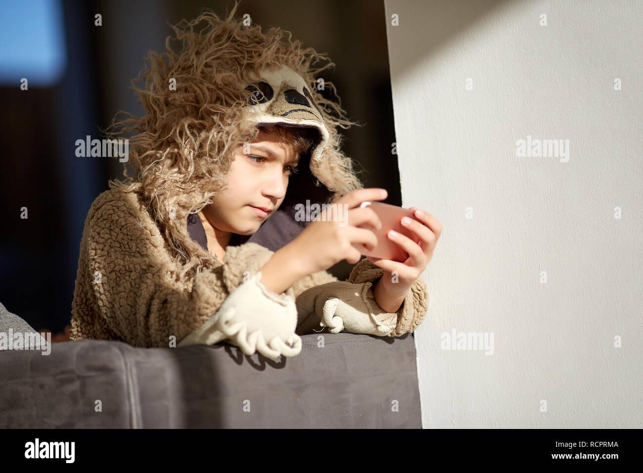 boy in sloth pajamas playing mobile phone - Stock Image