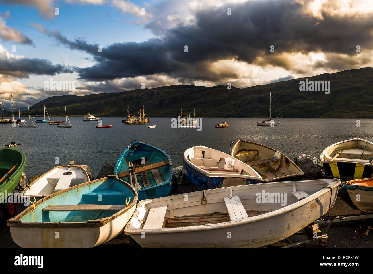 Old Small Rowing Boats At Loch Broom With Vintage Fisher Boats In The Harbor Of Ullapool In Scotland - Stock Image