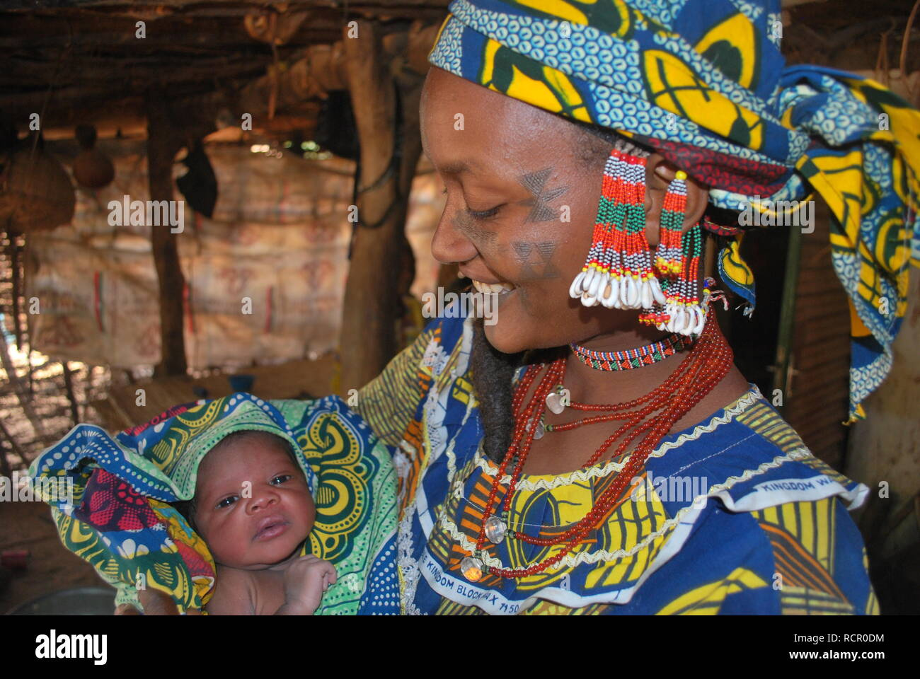 A young Fulani mother with traditional scars and jewellery cradling her newborn daughter in Niger, Africa. Stock Photo